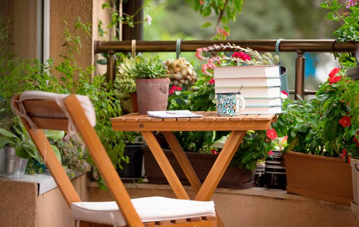 Kuva pienestä parvekepöydästä, jonka ympärillä on kasveja eri tasoilla. Parvekkeen sisustaminen on usein luovaa puuhaa.