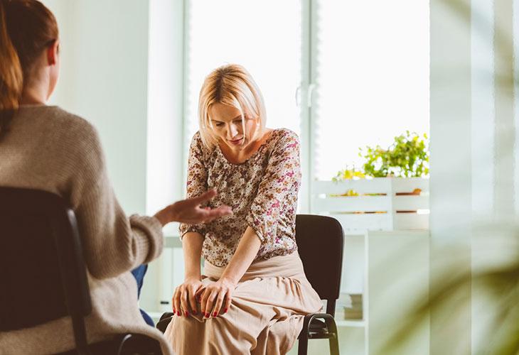 Sosiaalisten tilanteiden pelko voi oireilla esimerkiksi ahdistuksen kaltaisina tuntemuksina: kuvassa nainen istuu tuolilla ja pitelee polviaan ahdistuneen oloisena.