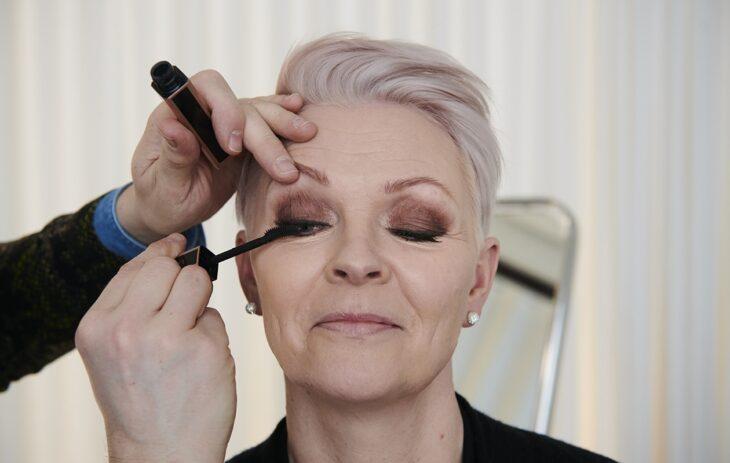 Annan Muuttumisleikin osallistujaa Annette Romusta meikataan.