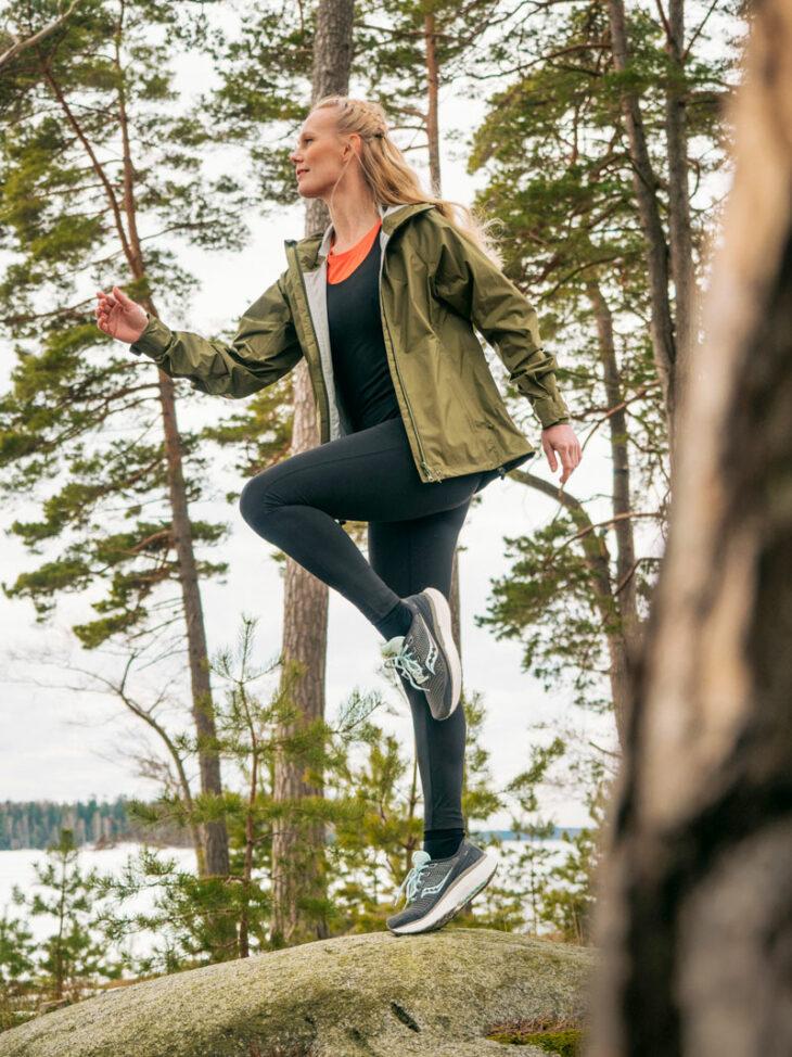 Nainen hypähtelee kalliolla yllään tekninen treenihaalari.