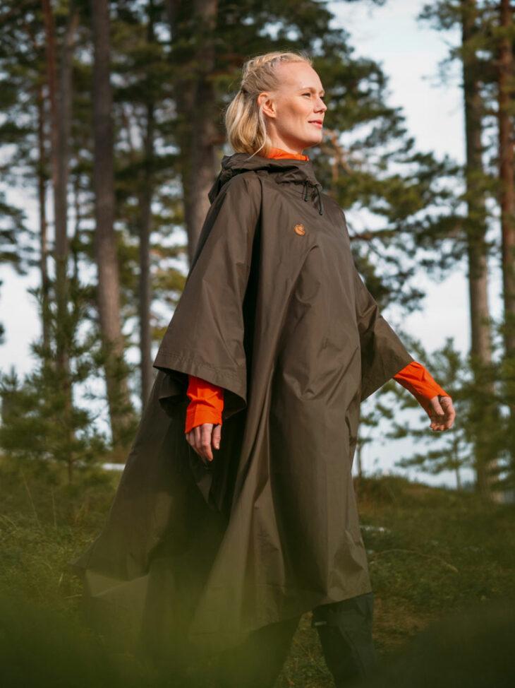 Nainen kulkee metsässä poncho yllään.