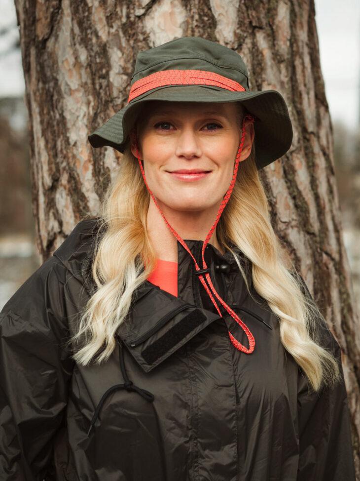 Nainen seisoo metsässä puun edessä päässään hattu.
