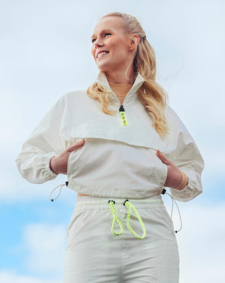Nainen seisoo vaaleansävyisessä, teknisessä urheiluasussa.