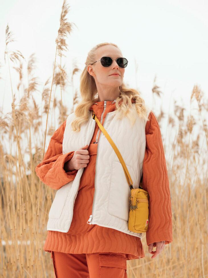 Nainen seisoo pellolla yllään oranssi tikkianorakki ja valkoinen tikkiliivi.