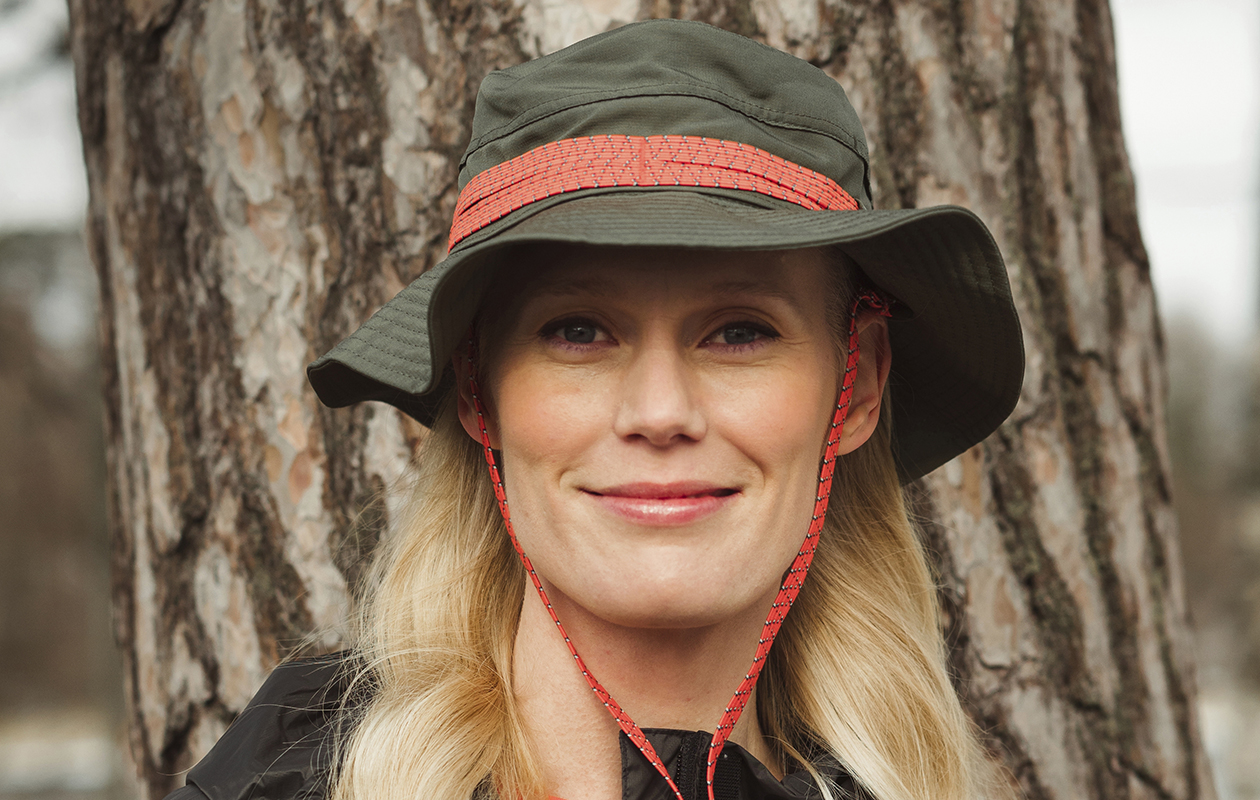 Nainen seisoo metsässä retkeilyhattu päässään.