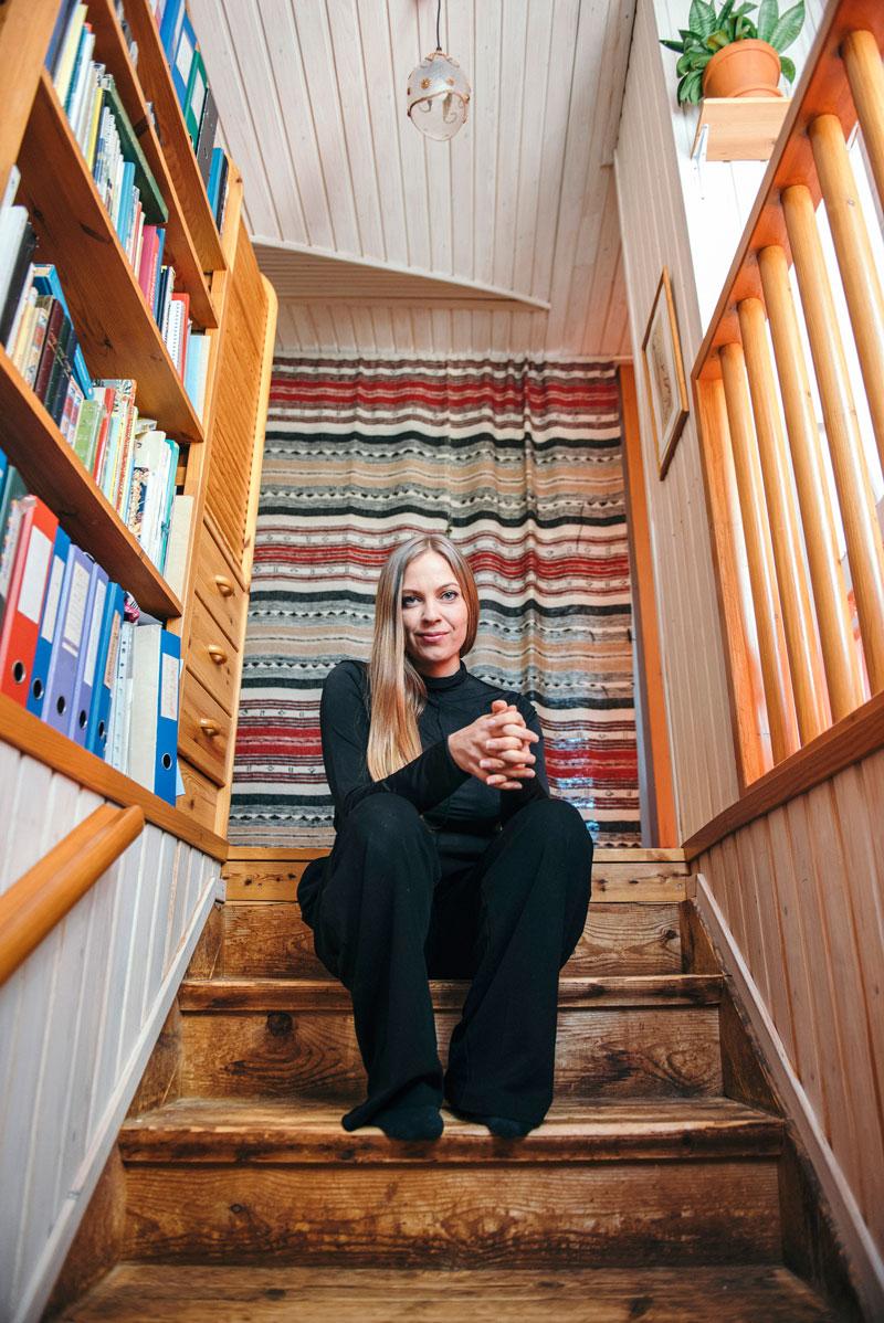 Kaisa Beltran istuu talon sisärappusilla.