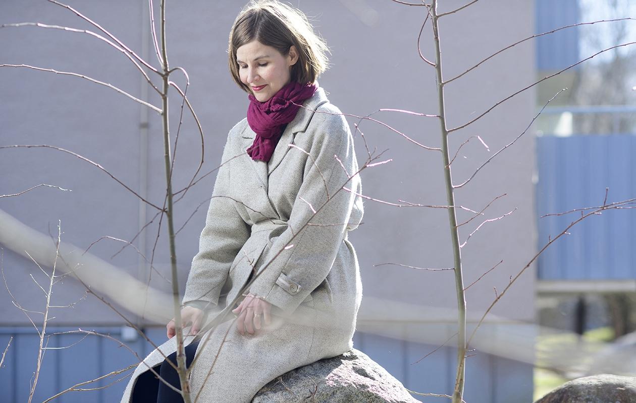 Laura Pörsti on pukeutunut isoäitinsä vanhaan harmaaseen villakangastakkiin. Takki on osa isoäidin tarinaa, ja Laura kirjoittaa siitä Viimeinen vuosi -kirjassaan.