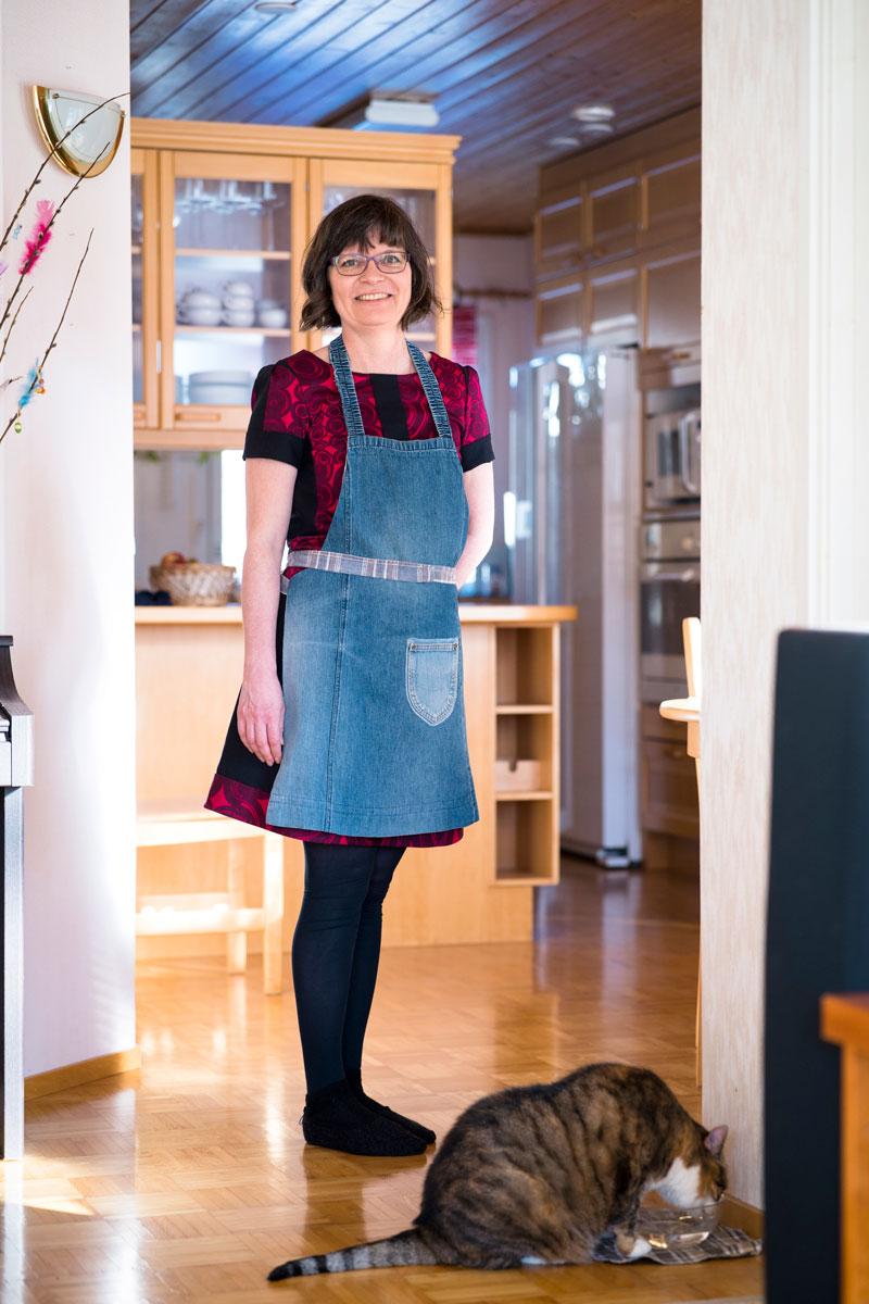 Kirsi Peltola seisoo keittiössään esiliina yllään. Hänen jaloissaan kissa juo vettä kupista.