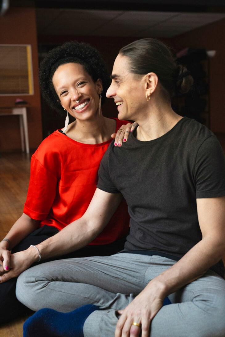 Petri Räisänen ja Wambui Njuguna-Räisänen istuvat joogasalin lattialla ja hymyilevät leveästi.