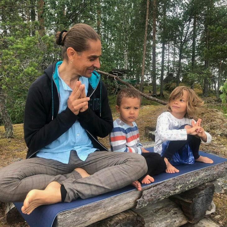 Petri Räisänen istuu metsässä puusta tehdyllä penkillä poikiensa Sumun ja Sesamin kanssa.