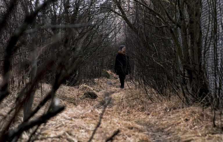 Nainen seisoo tunnistamattomana metsässä.