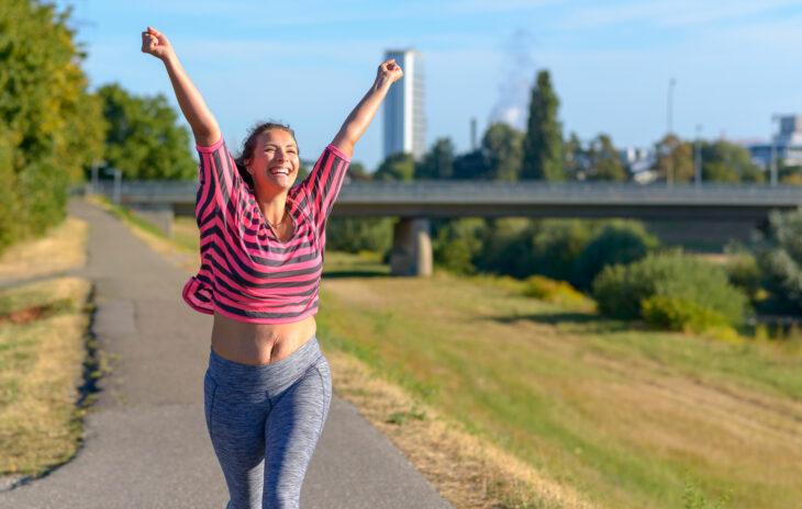 Juoksuohjelma 5 km matkalle – nainen tuulettaa saavutettuaan juoksutavoitteen