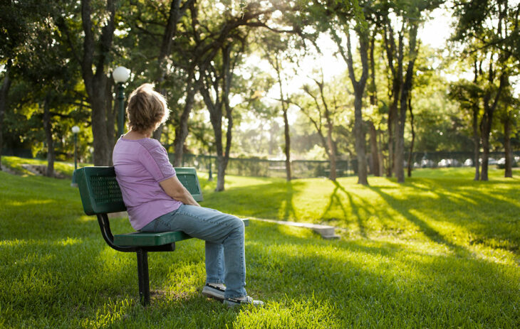 Vaikea äitisuhde voi olla raskas taakka, mutta taakkaa on myös mahdollista keventää, yksinkin. Kuvassa nainen istuu yksin puistonpenkillä.