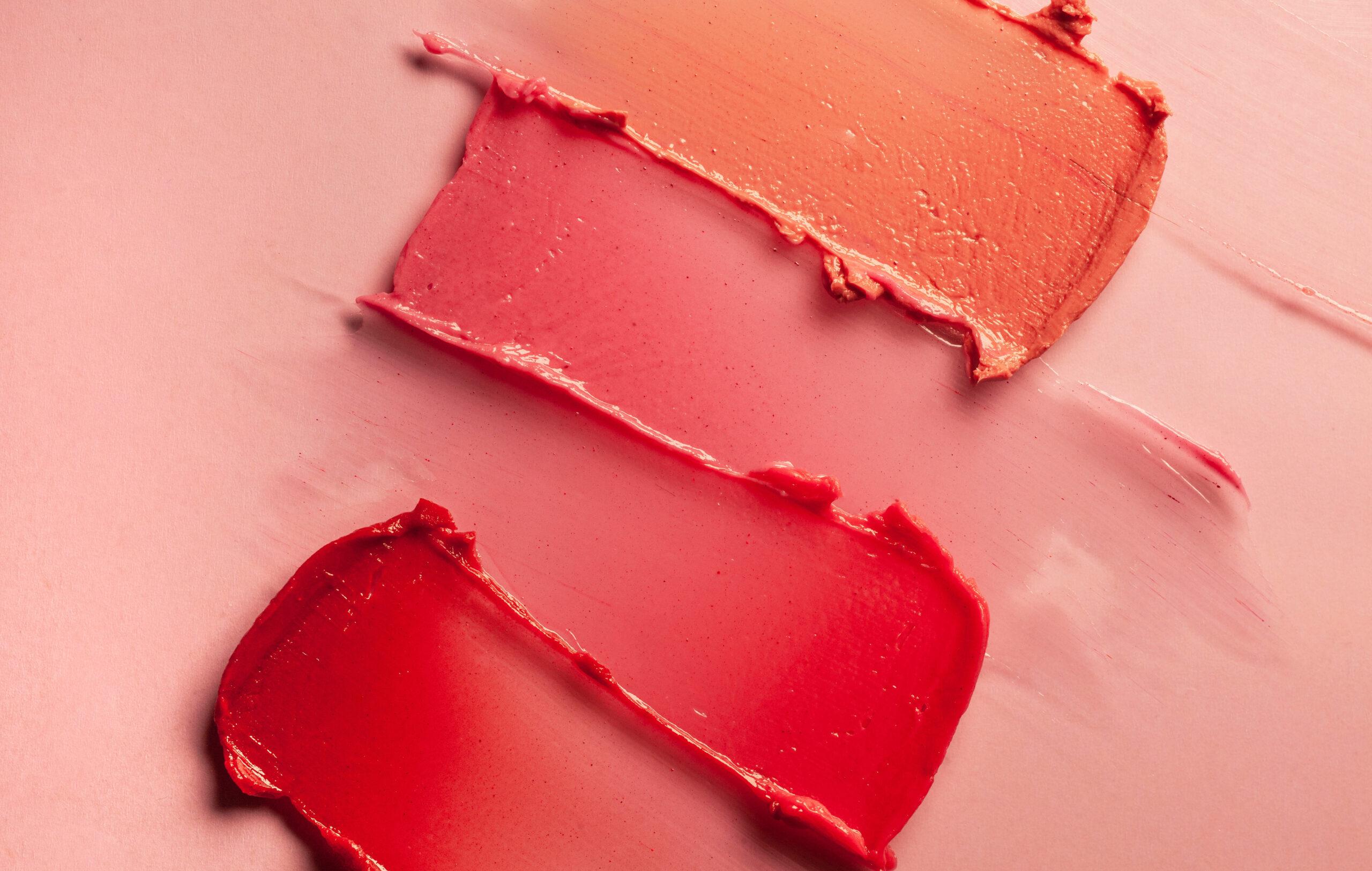 Huulipunasävyjä sudittuna vaaleanpunaiselle taustalle.