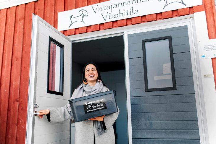 Vuohenmaitoyrittäjä Shirin Namiq seisoo Vatajanrannan vuohitilan ovella laatikko sylissään ja hymyilee.