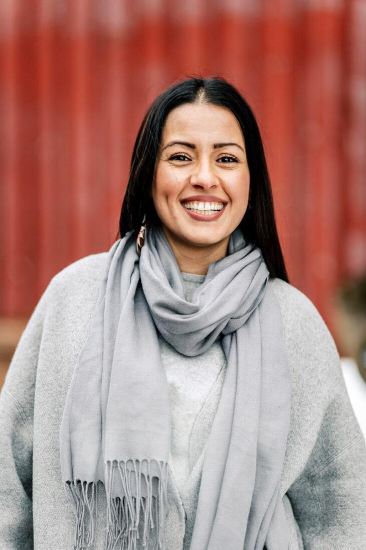 Shirin Namiq hymyilee leveästi yllään harmaa takki ja kaulaliina.