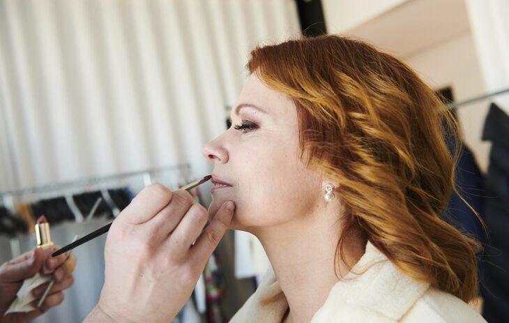 Maskeeraaja levittää Mari Kärkkäiselle huulipunaa siveltimellä.