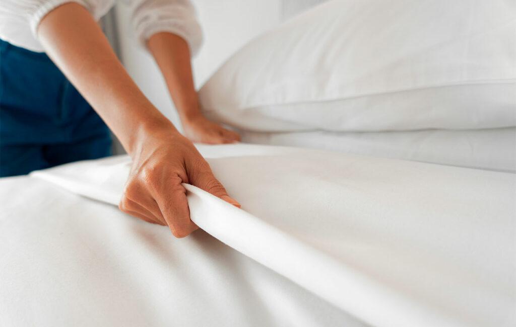 Lähikuva ihmisen kädestä, joka asettelee lakanoita sängylle.