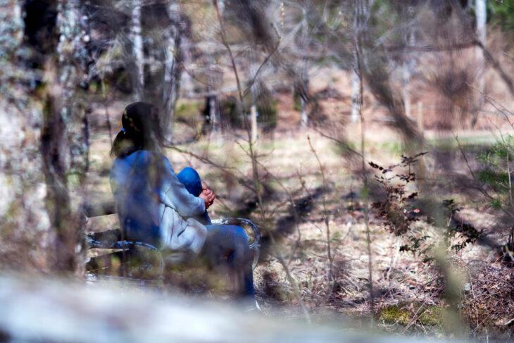 Nainen istuu puiston penkillä.