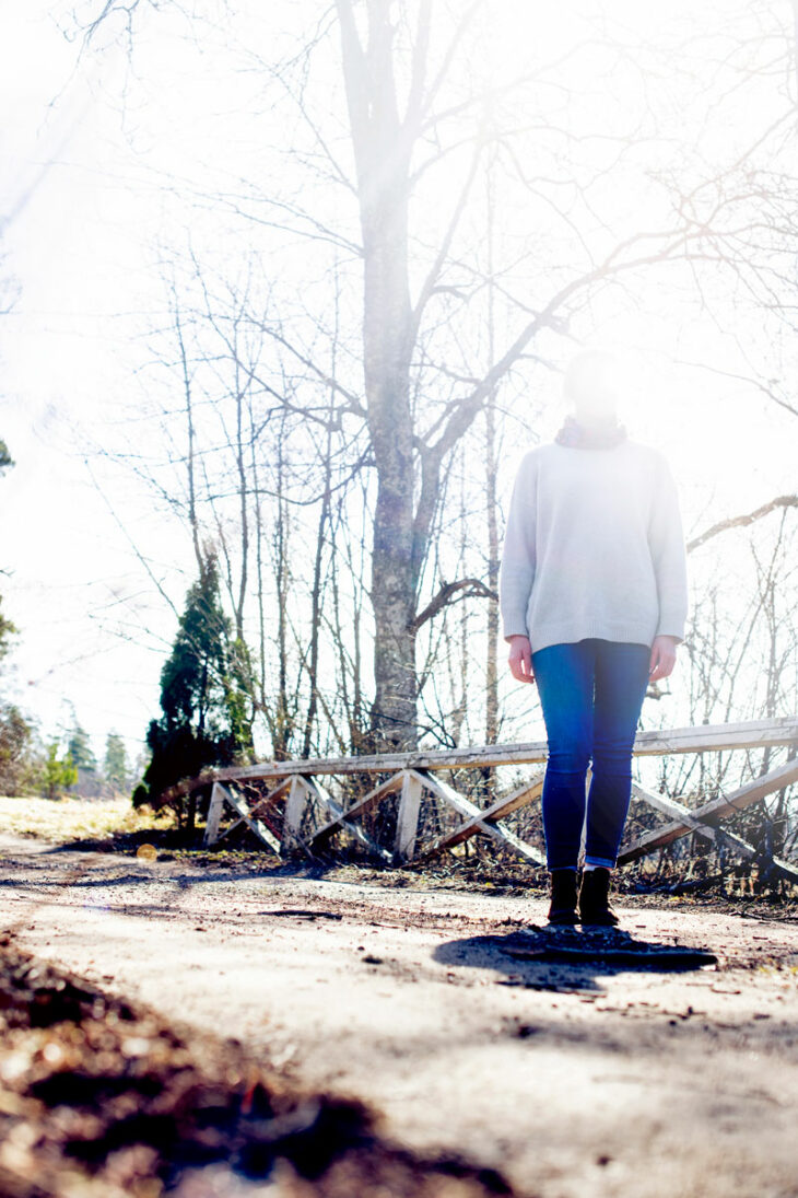Nainen seisoo metsätiellä.