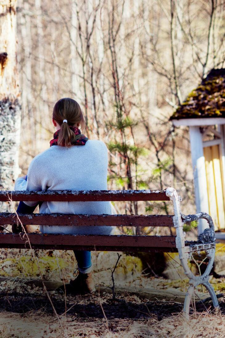 Nainen istuu puiston penkillä selin.
