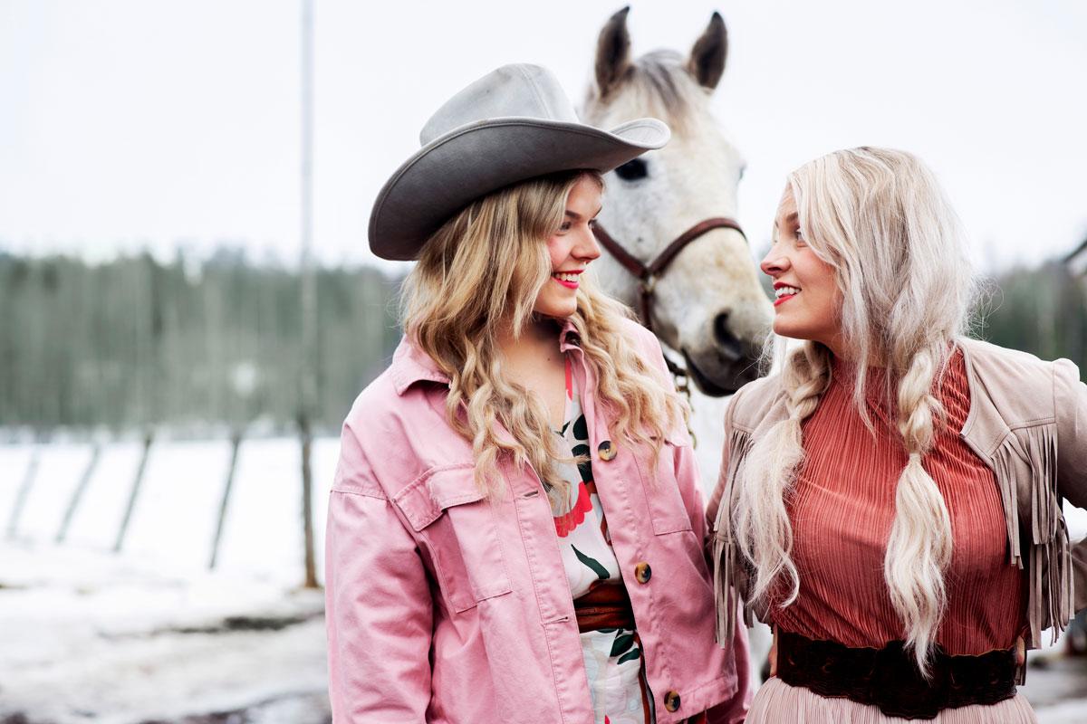 Lili & Luna -duon jäsenet Sanni Savolainen ja Leena Tirronen katsovat toisiinsa. Heidän välistään kurkistelee hevonen.
