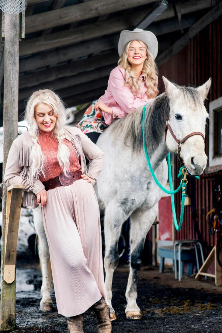 Leena Tirronen nojaa puuaitaan tallissa. Hänen vieressään Sanni istuu hevosen selässä.