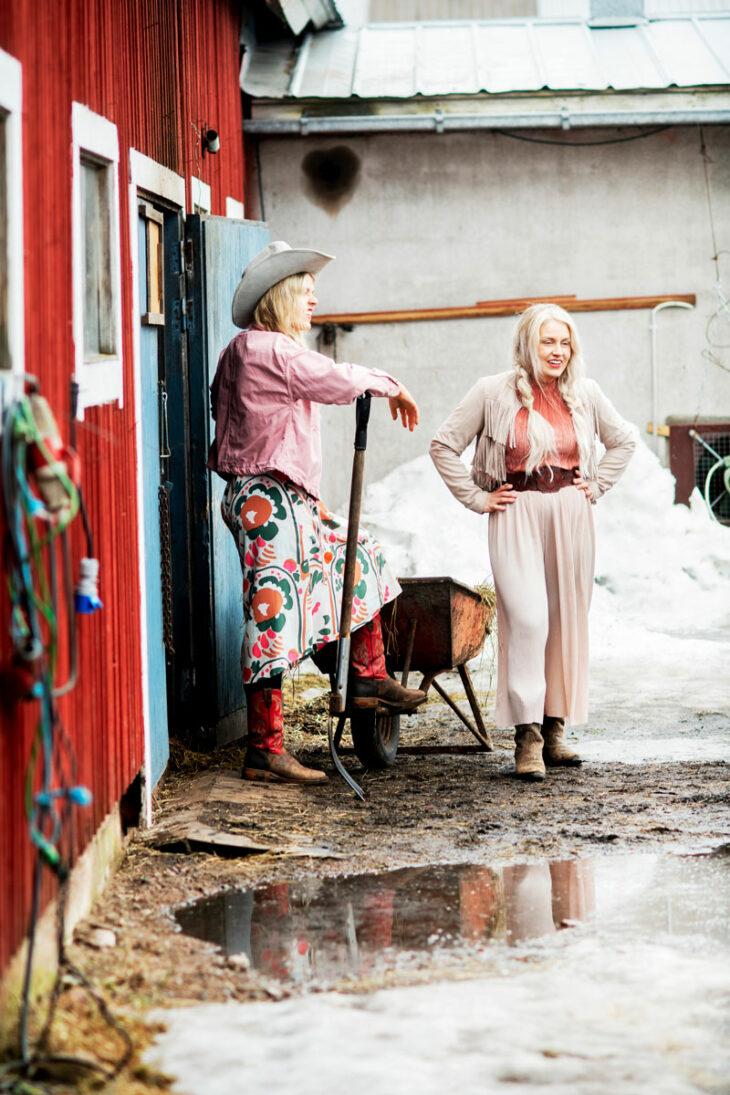Sanni Savolainen nojaa talikkoon ja Leena Tirronen seisoo hänen vieressään kädet puuskassa.