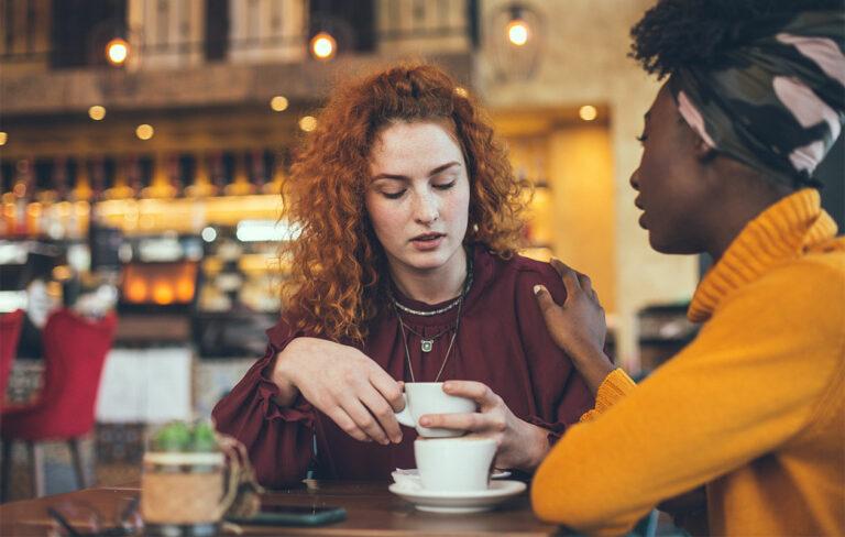 Ystävyksen kahvilla, toinen pitää kättä toisen olkapäällä.