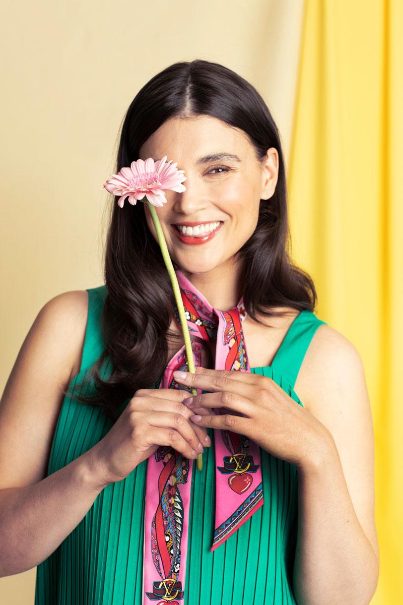 Mallilla on yllään vihreä kesätoppi, kirjava huivi ja vaaleanpunainen kukka.