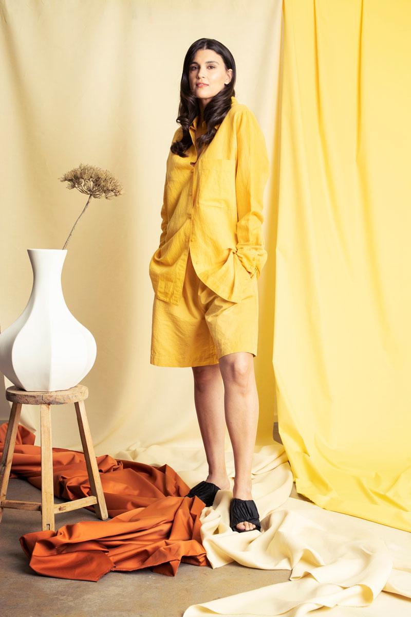 Malli seisoo yllään keltainen sortsiasu.
