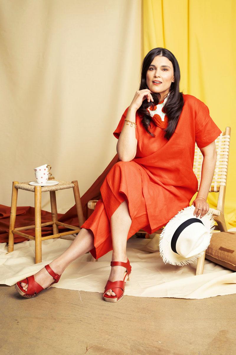 Nainen istuu tuolissa yllään punaoranssi paitamekko sekä samansävyiset culottes-housut ja puukengät.