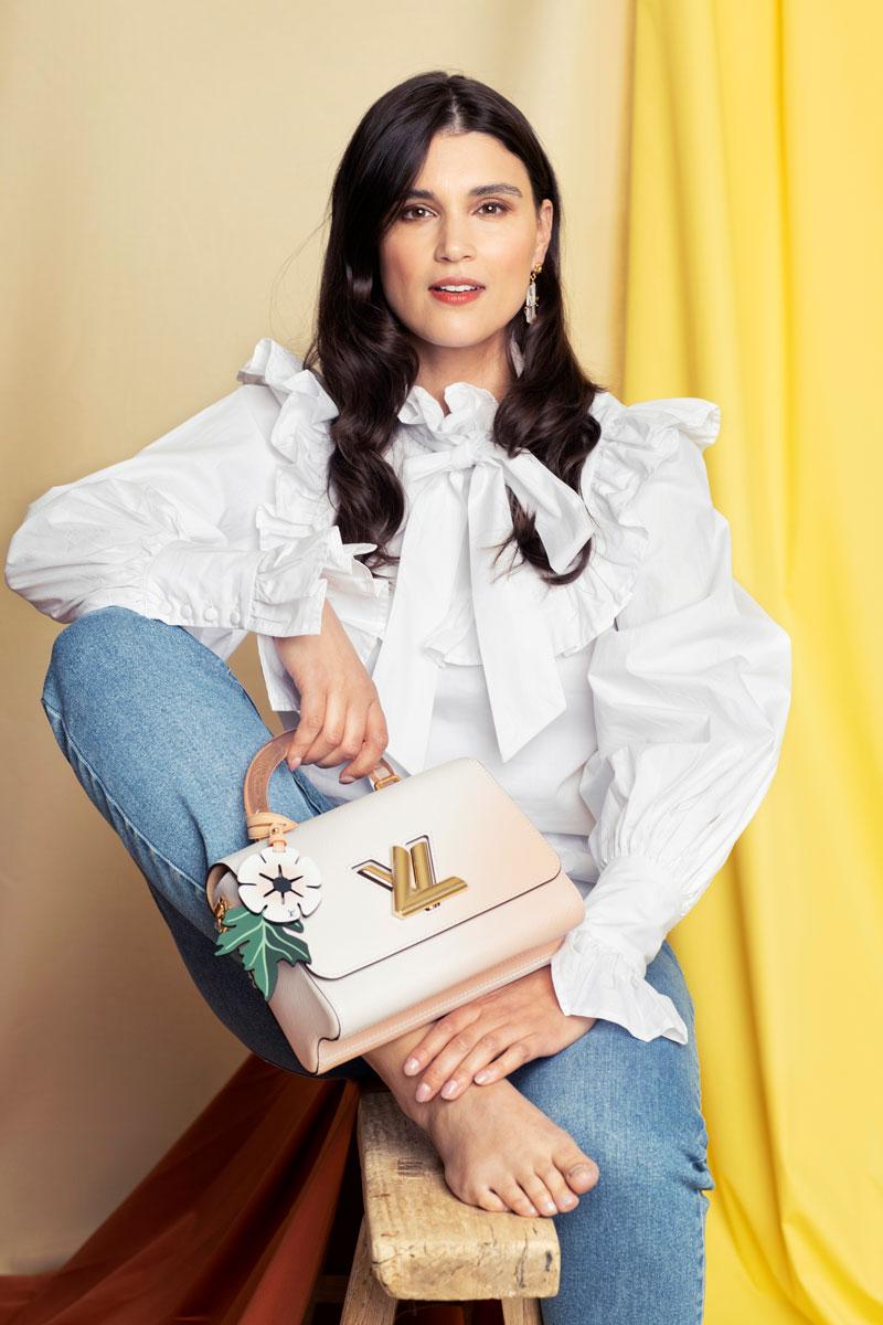 Nainen istuu yllään valkoinen, röyhelöinen paitapusero, siniset farkut ja käsilaukku.