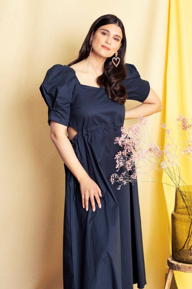 Naisella on yllään tummansininen mekko, jossa on muhkeat hihat ja leikkaukset kyljissä.