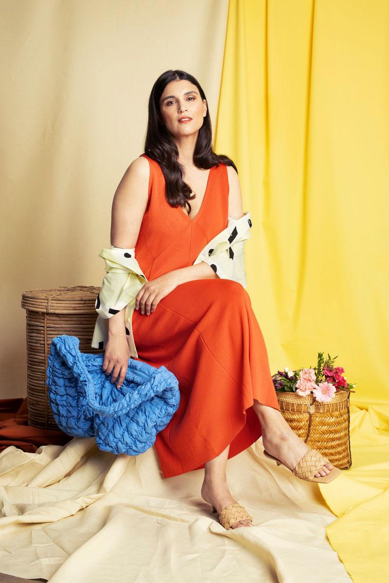 Nainen istuu yllään oranssi, pitkä neulemekko.