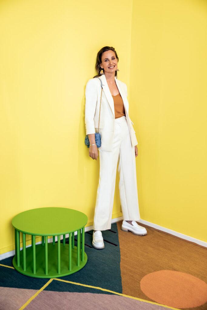 Nainen nojaa seinään yllään valkoinen housupuku.