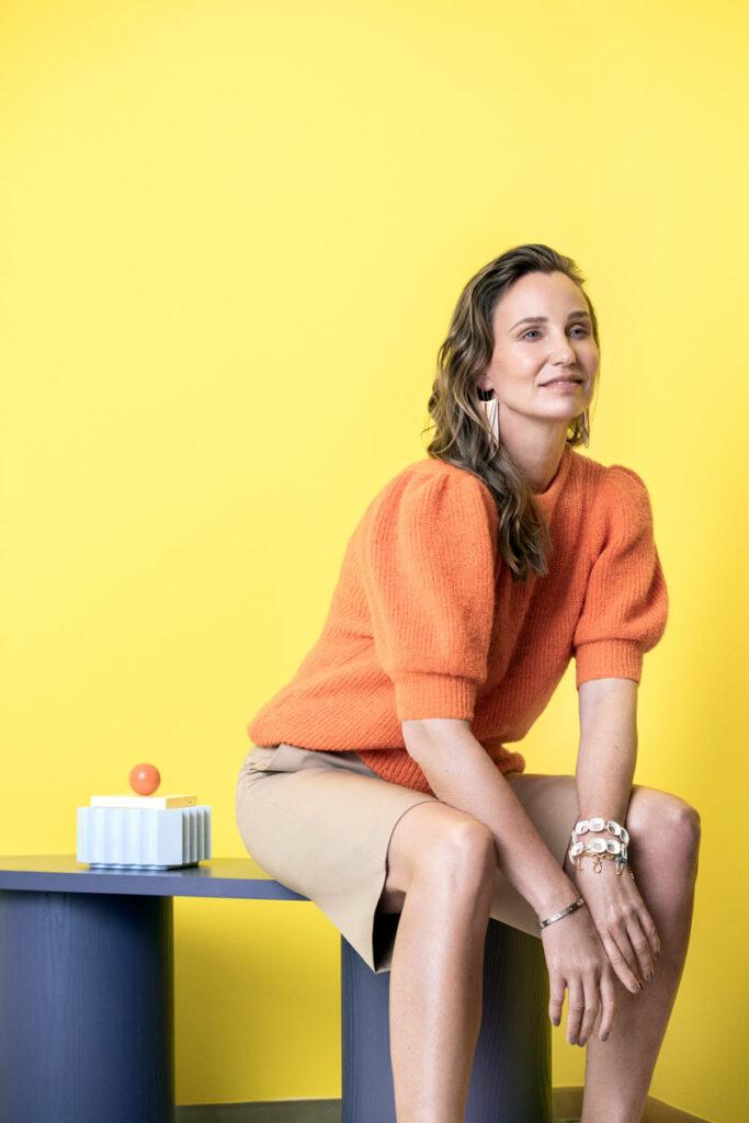Nainen istuu yllään oranssi, pussihihainen kesäneule. Jalassa on kapeat, polvipituiset sortsit.