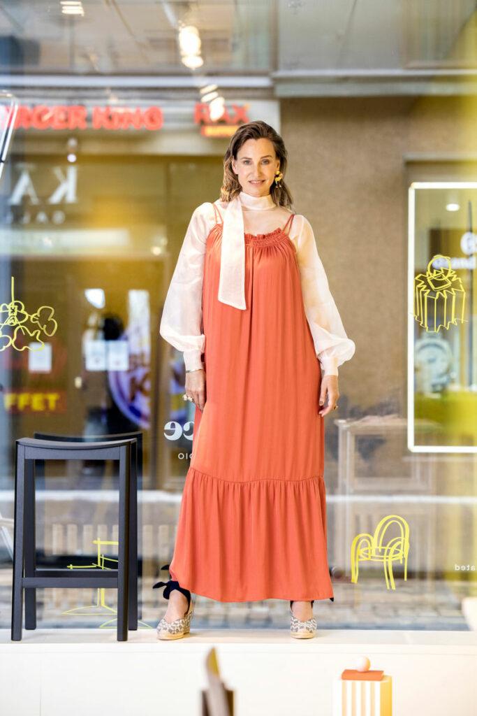 Nainen seisoo yllään oranssi maksimekko, jonka alla on näyttävä silkkiorganzapusero.