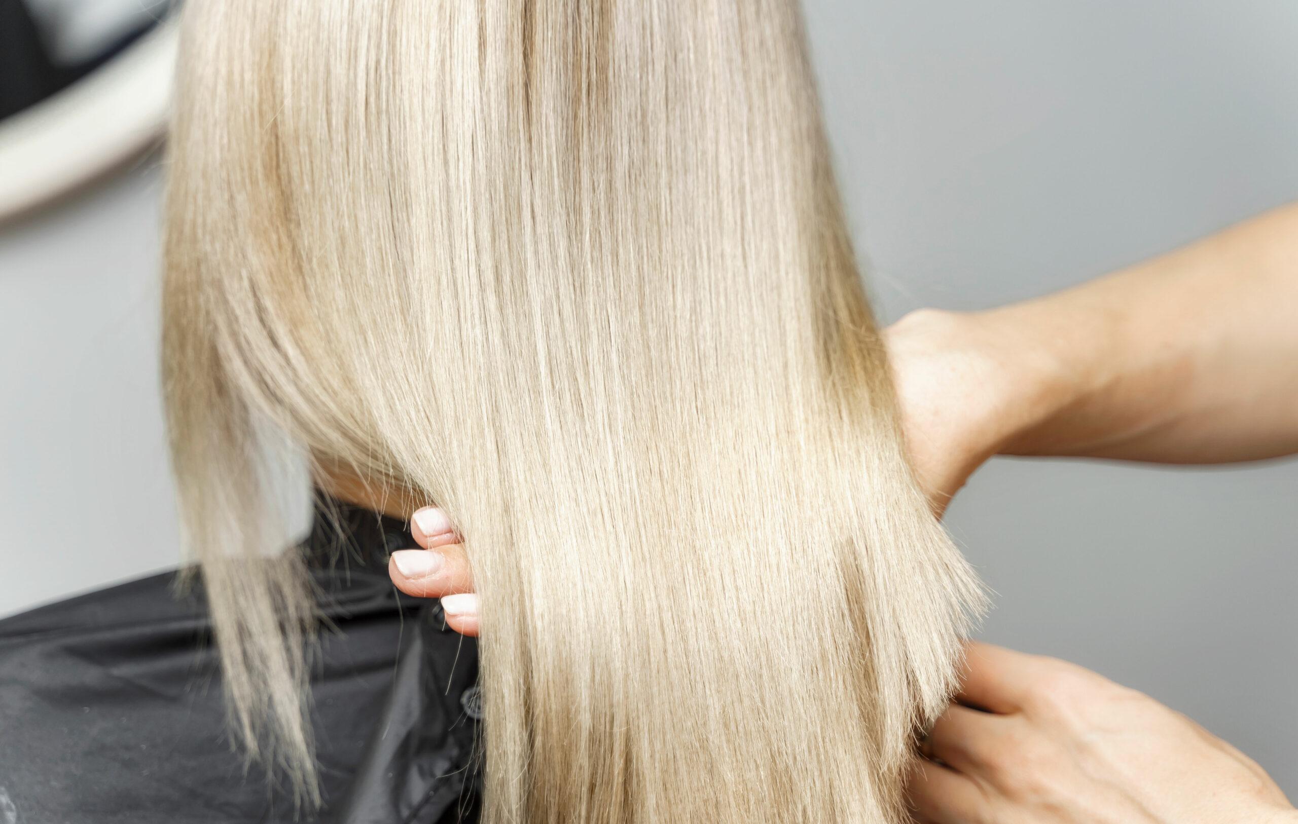 Vaaleahiuksinen ihminen kampaajan tuolissa – Olaplex ja muut hiusten tehohoidot tehdään kampaajalla.