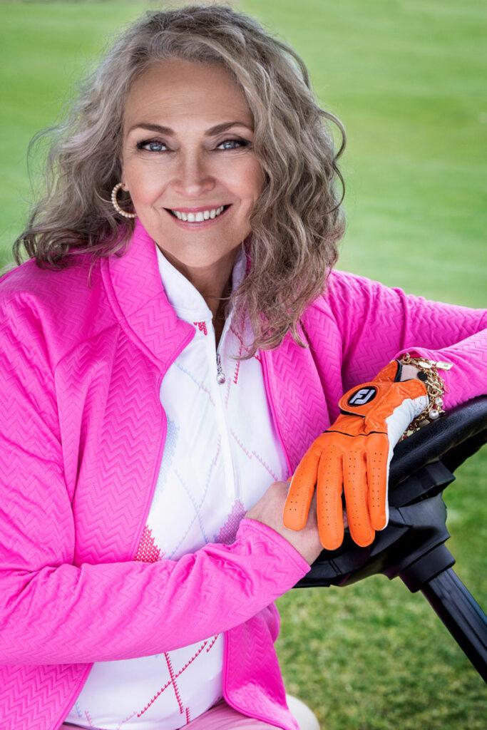 Malli istuu golfautossa kuskin penkillä. Hänen yllään on pinkki verkkatakki. Kädessä on golfkäsine.