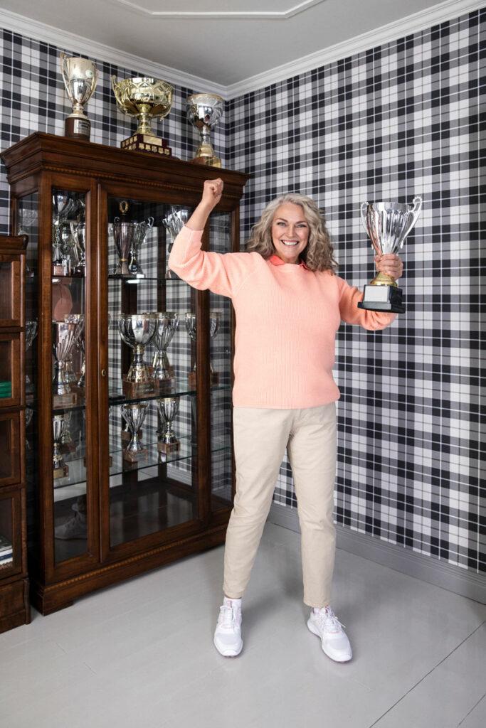 Nainen tuulettaa voittoa pokaali kädessään. Yllään hänellä on vaaleanoranssi neule, beiget chinot ja golftossut.