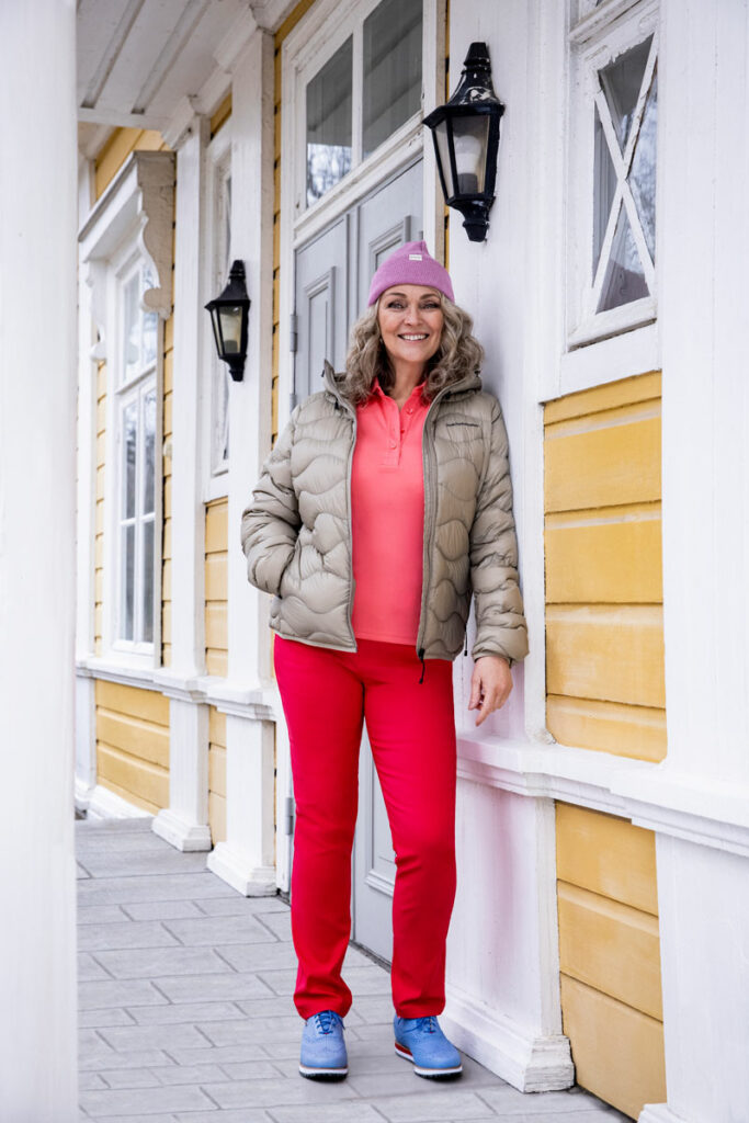 Nainen seisoo yllään kevytuntuvatakki, punaiset housut ja siniset golfkengät. Päässään hänellä on vaaleanvioletti pipo.