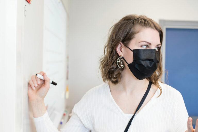 Lappeenrannan Kimpisen koulun yläasteen äidinkielen opettaja Heidi Selenius, 36, seisoo kynä kädessään taulun edessä. Kasvoillaan hänellä on musta maski.