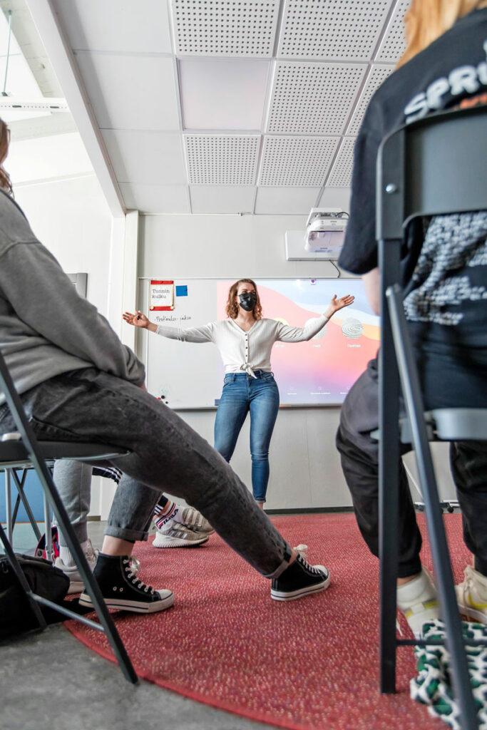 Opettaja Heidi Selenius seisoo luokan edessä kädet levällään.