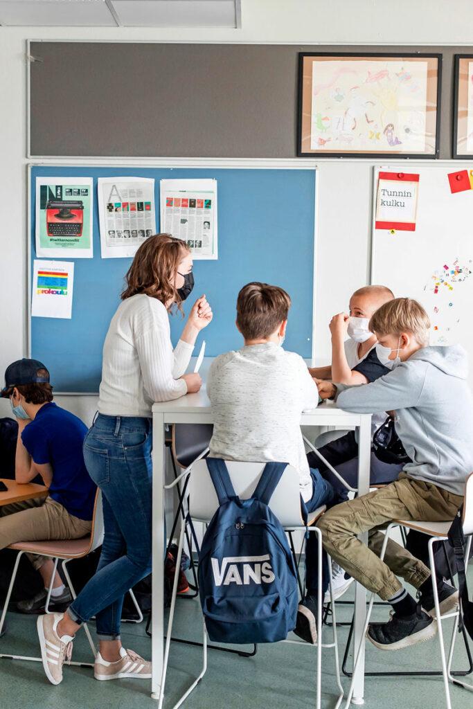 Opettaja Heidi Selenius seisoo pöydän vieressä ja keskustelee kolmen oppilaansa kanssa.