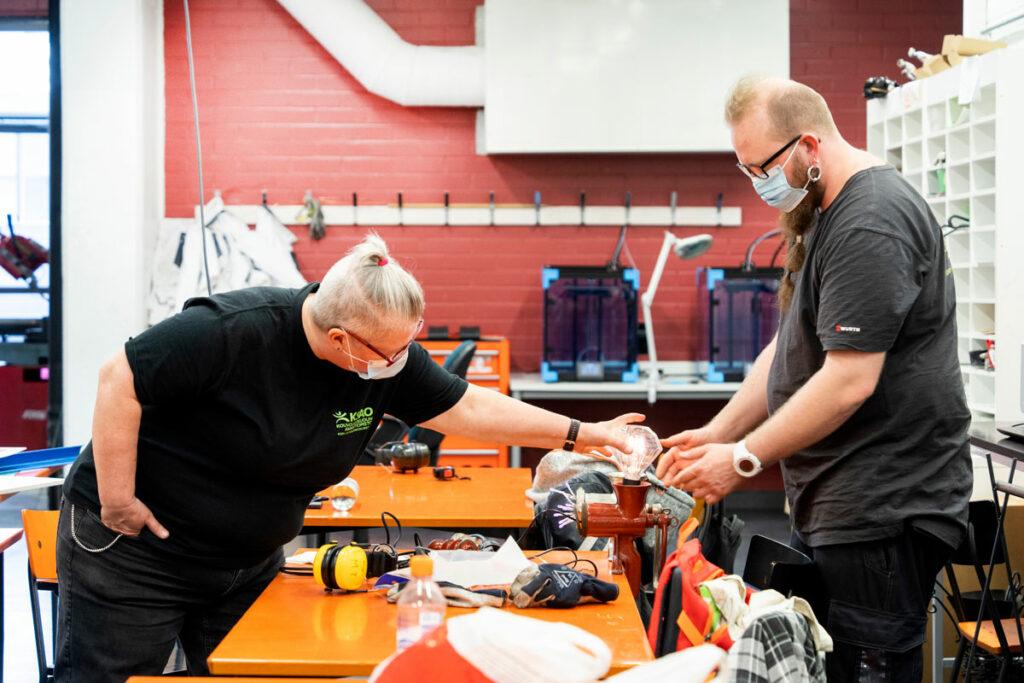 Opettaja Merja Salminen-Itkonen ja opiskelija Martti Ylätupa mallaavat valaisimeen timantin muotoista lamppua.