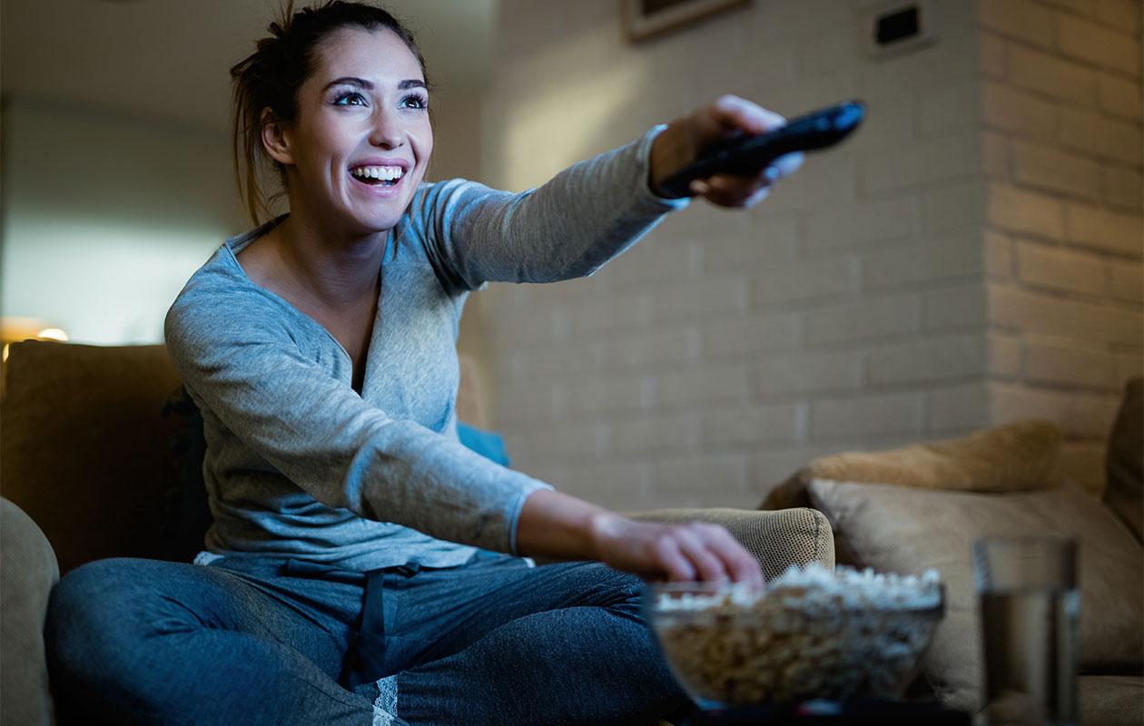 Nainen osoittaa nauraen kaukosäätimellä television suuntaan.
