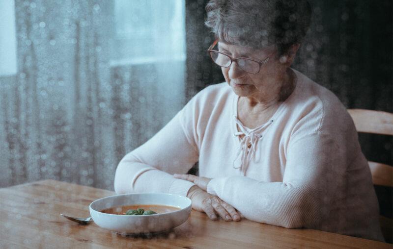 Sateisen ikkunan takaa otettu kuva vanhemmasta naisesta, joka katsoo keittolautasta. Aikuisten syömishäiriöt voivat koskettaa minkä ikäisiä ihmisiä tahansa.