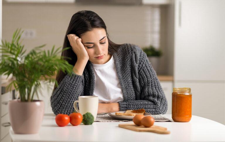 Nainen katsoo pohtien pöydällä olevia ruokia.