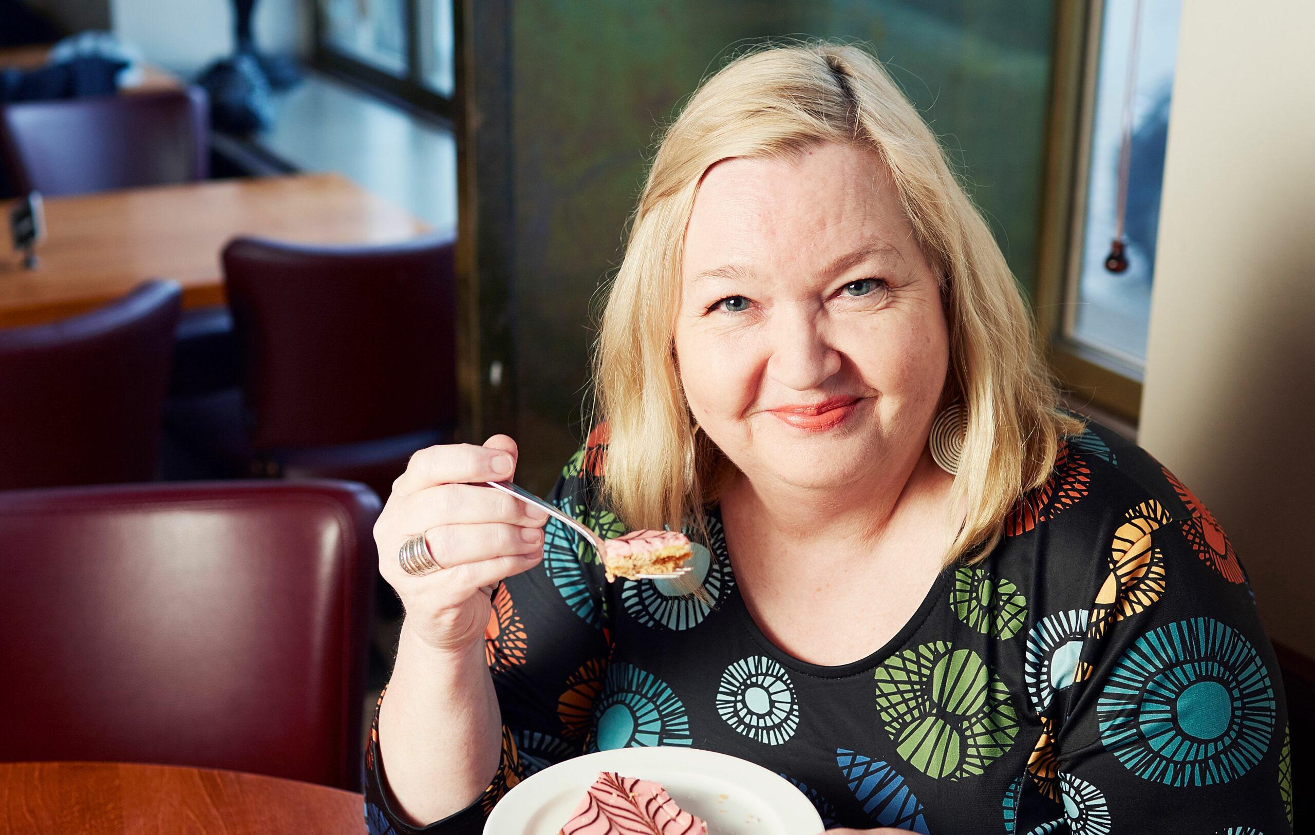 Kirjailija Regina Rask istuu pöydän ääressä syömässä leivosta.
